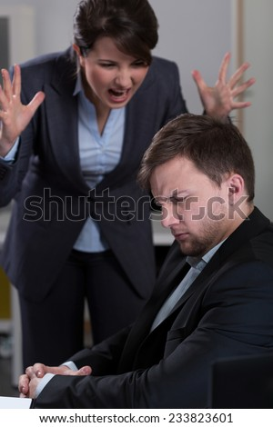 Young female boss yelling at her handsome worker - stock photo