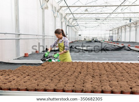 Young female botanist seeding plants in greenhouse