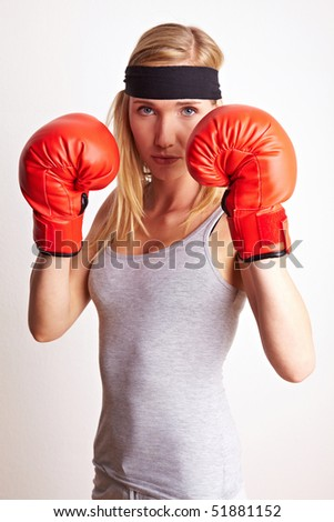 Young female boxer with red boxing gloves and headband