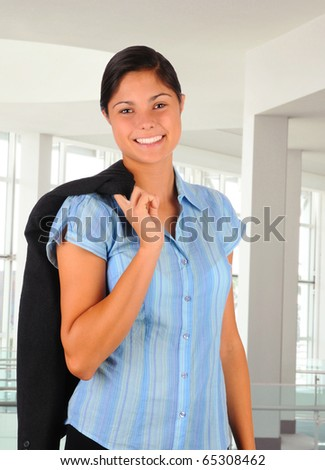 Young female business professional in modern office building holding her jacket over her shoulder. She is smiling in 3/4 view. Vertical format. - stock photo