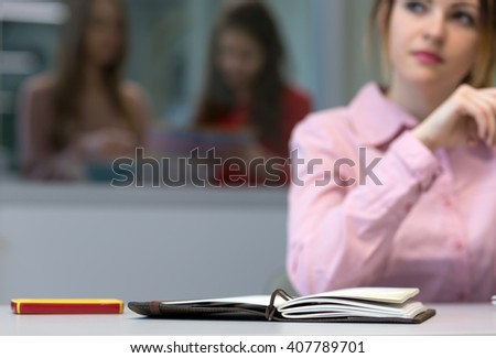 Young female Business Trainee working on Laptop Computer at grey Desk pensively looking aside thinking about new Idea - focus on Notepad face is blurred - stock photo