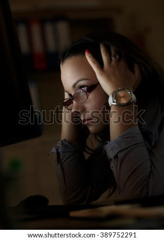 Young female business woman working at home.She works late into the night looking at monitor.  - stock photo