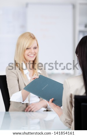 young female candidate in an interview in the office passing her CV - stock photo