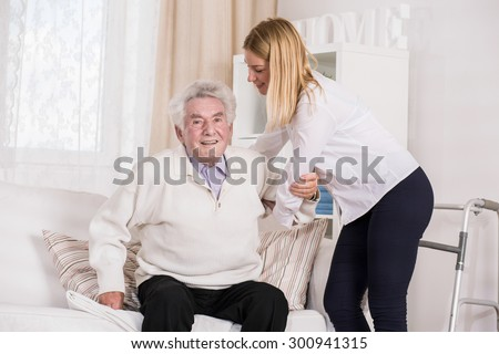 Young female care assistant helping senior man - stock photo