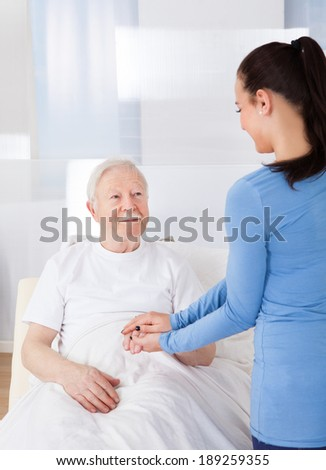 Young female caregiver consoling senior man at nursing home - stock photo