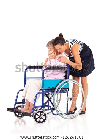 young female caregiver hugging and comforting lonely disabled senior woman