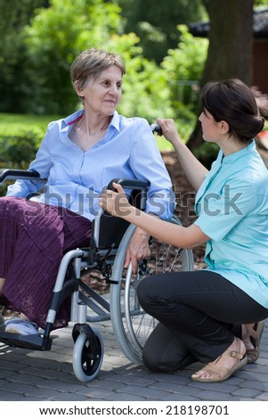 Young female caregiver talking with handicapped senior woman on wheelchair - stock photo
