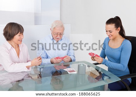 Young female caretaker playing cards with senior couple at table in nursing home - stock photo