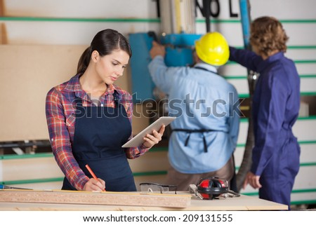 Young female carpenter holding digital tablet while coworkers working in background at workshop - stock photo