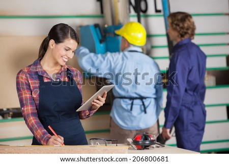 Young female carpenter using digital tablet while coworkers working in background at workshop - stock photo