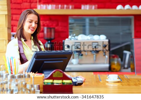 young female cashier operating at the cash desk in cafe - stock photo