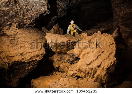 Young female caver exploring the cave. Mlynky Cave, Ukraine - stock photo