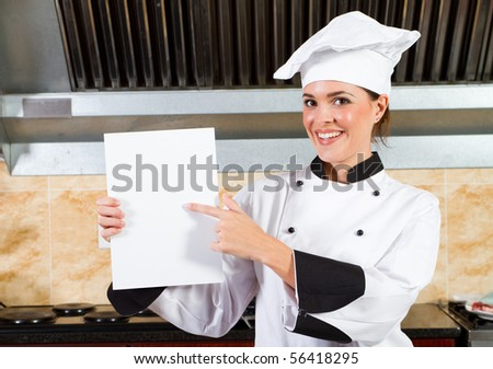 young female chef holding a white board or menu in kitchen - stock photo
