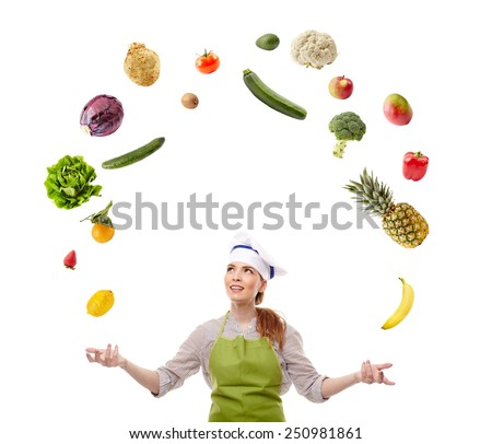 Young female chef juggling with many fruits and vegetables isolated on white background - stock photo