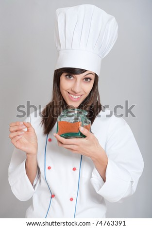 Young female chef with an open red spice pot - stock photo