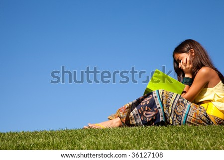 young female child at the park reading a book - stock photo