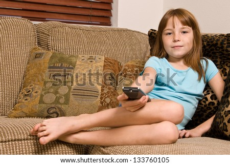 Young female child holding a remote while watching television
