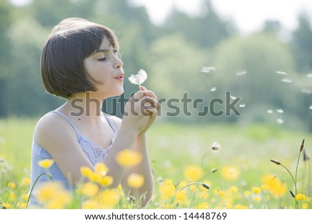 young female child sitting in field of buttercups blowing a dandelion with room for copy