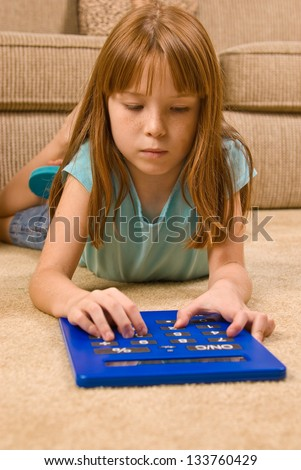 Young female child works on an oversized calculator