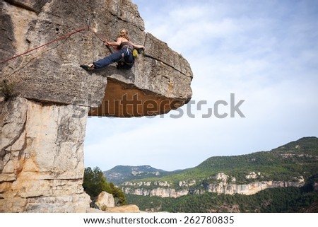 Young female climber on a cliff  - stock photo
