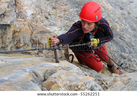 Young female climber with red helmet - stock photo