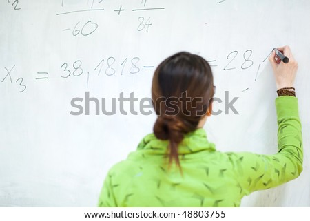 young female college student in front of a whiteboard during a math class - stock photo