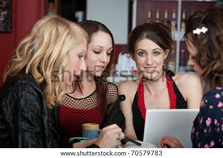 Young female college student studying with three friends in a cafe