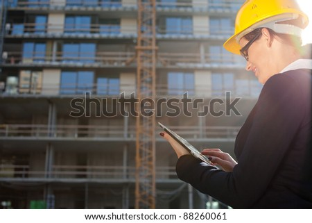 Young female construction specialist reviewing blueprints at construction site - stock photo