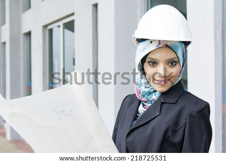 Young female construction specialist with a blueprints - stock photo