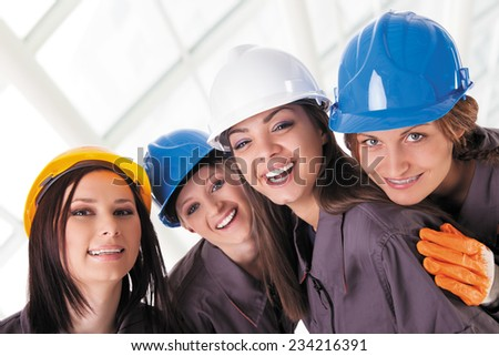 Young female construction workers with protective clothes and helmets. Isolated with work path. - stock photo