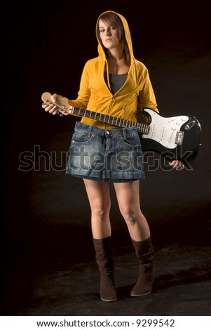 Young female covering herself with skirt hanging from guitar - stock photo