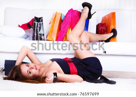 Young female customer in a dress lying on the floor. - stock photo
