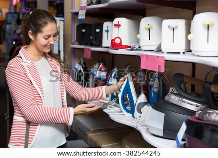 Young female customer looking at irons in domestic appliances section