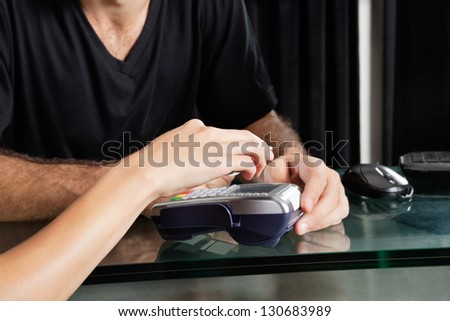 Young female customer paying with mobilephone over electronic reader at salon - stock photo