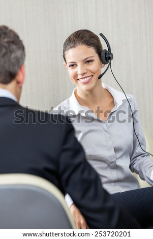 Young female customer service executive wearing headset while looking at manager in office - stock photo
