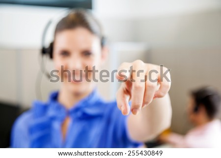Young female customer service representative pointing at you in office - stock photo