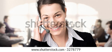Young female customer service representative receives calls on a headset while colleagues are working on computers in the background. - stock photo