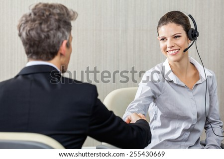 Young female customer service representative wearing headset while shaking hands with manager in office - stock photo
