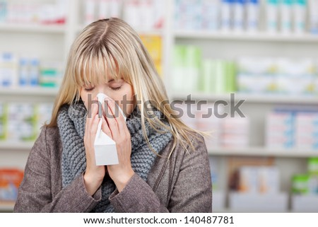 Young female customer suffering from cold in pharmacy - stock photo