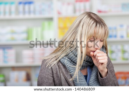 Young female customer with eyes closed coughing in pharmacy - stock photo