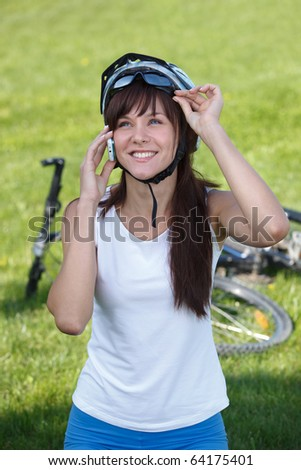 Young female cyclist making a call on the grass background