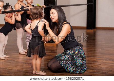 Young female dance instructor comforting one of her younger ballet students during a dance class - stock photo