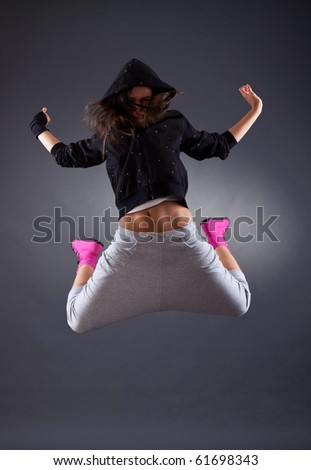 young female dancer jumping on the grey background