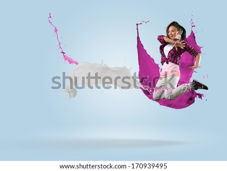 young female dancer jumping surrounded by splashes of paint - stock photo