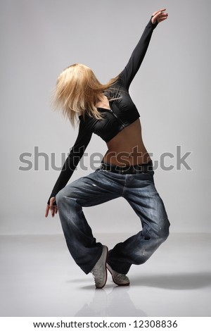 young female dancing on the grey background - stock photo