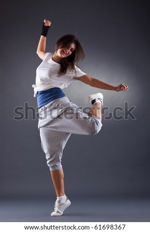 young female dancing on the grey background