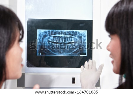 Young female dentist examining patient teeth X Ray