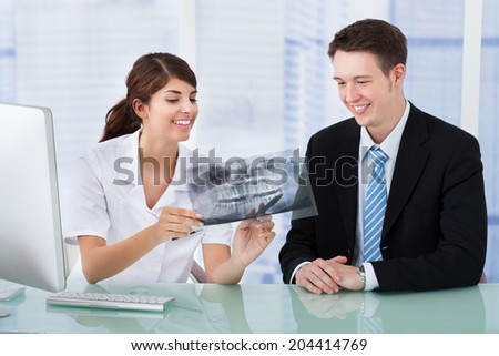 Young female dentist showing jaw Xray to businessman in clinic - stock photo