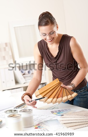 Young female designer at office with wooden color swatches - stock photo
