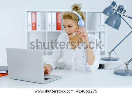 Young female dispatcher working, using laptop, wearing headphones, talking, smiling. - stock photo